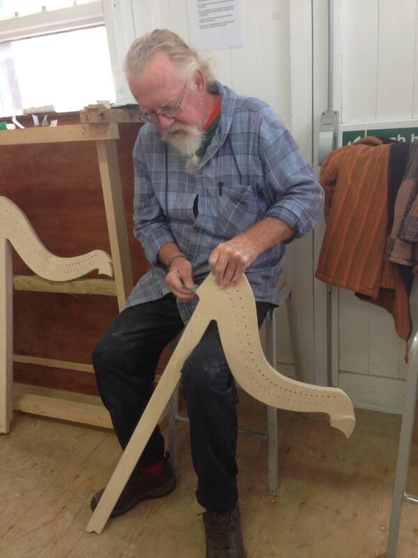 man repairing harp